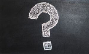 A chalk drawing of a question mark on a blackboard.